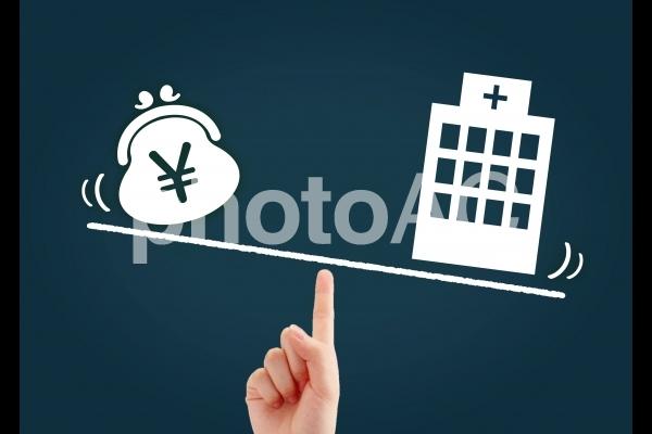病院とお金の天秤イメージの写真