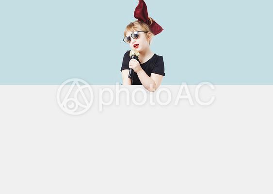マイクで歌うサングラスの女の子の写真