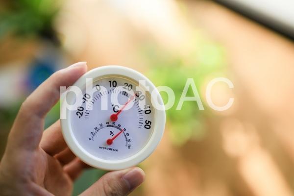 温度計を持つ人の写真