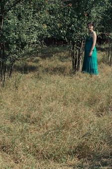 外国 海外 屋外 野外 自然 人物 1人 外国人 白人 セルビア人 大人 若い 女性 女 女の子 ブルネット 黒髪 セミロング まとめ髪 ひっつめ髪 無造作ヘア 普段着 青緑の服 ワンピース ロングワンピース ノースリーブ キャミソールワンピース 低木 木 果樹 木立 芝生 mdff021