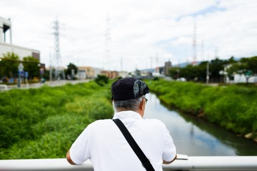 川を眺めるシニア男性の写真