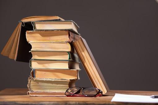 屋内 無人 机 デスク テーブル 木 小物 机上 本 重なる 重ねる 積む  見開き 開く  眼鏡 メガネ めがね  学習 勉強 知識 知的 情報 レトロ クラシック 古い ほころび  思い出 古書 読書
