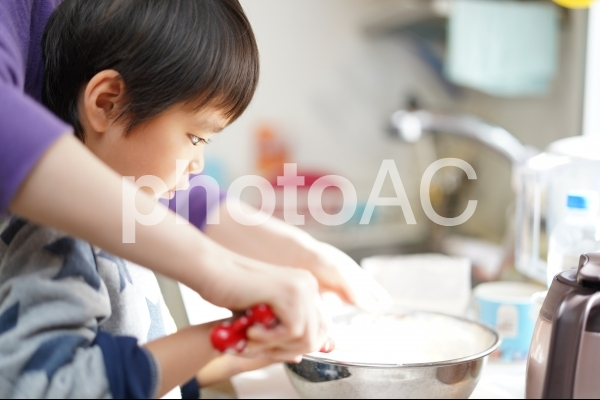 おうち時間中にパンケーキ作りのお手伝いをする子どもの写真