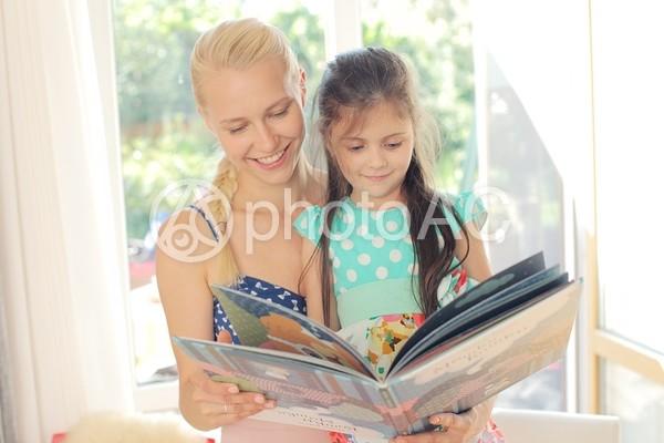 女の子と絵本を読むワンピースの女性3の写真