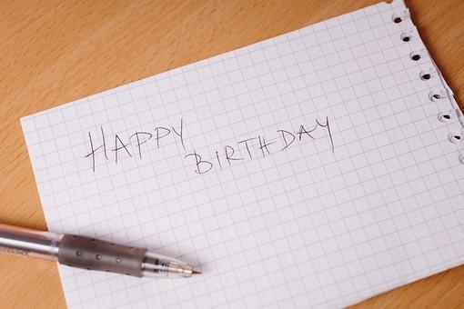 バースデーカード ボールペン 紙 手帳 ノート 方眼 走り書き 手書き 直筆 ボールペン 黒 思いやり 真心 文字 誕生日 誕生祝 ハッピーバースデー 英語 テーブル ベージュ 木目 置く 物撮り 人物なし 室内 上から視線 1本 複数 Happy Birthday