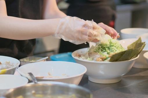 厨房で調理をする女性の手の写真