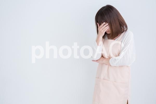 泣くエプロン姿の女性の写真