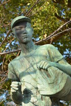 像 彫刻 ブロンズ像 銅像 人物 少年 置物 置き物 飾り アップ クローズアップ 接写 芸術 アート 作品 美術 細かい 細工 公園 屋外 外 公共 自然 樹木 植物