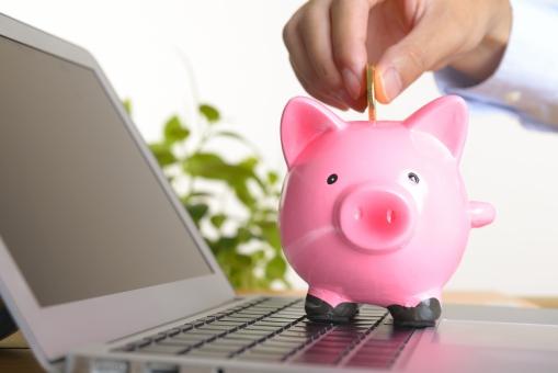 パソコンと豚の貯金箱の写真