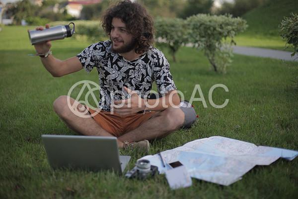芝生の上でパソコンを使う男性4の写真