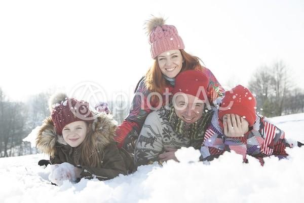 雪の上に寝転ぶ家族13の写真