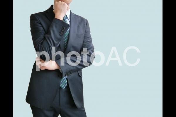 悩むポーズをとるビジネスマン-青背景の写真