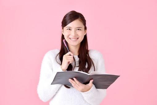 人物 女性 日本人 若者 若い  20代 美人 かわいい ロングヘア カジュアル  ラフ 私服 セーター ニット 屋内  スタジオ撮影 背景 ピンク ピンクバック ポーズ  おすすめ 上半身 ファイル ノート 勉強 考える ひらめく アイディア アイデア 笑顔 mdjf007