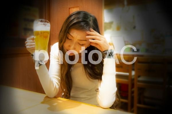 居酒屋で一人思い悩む女性の写真