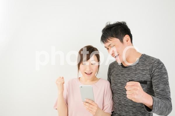 スマホを見てガッツポーズする男女の写真