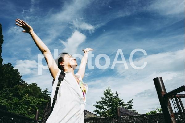 空に向かって手を広げる女性の写真