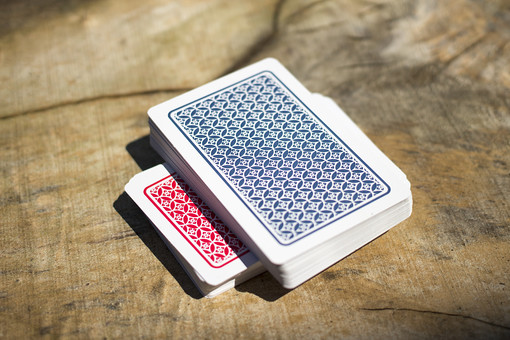 トランプ カード ゲーム 札 娯楽 木 屋外 茶色 机 テーブル 赤 裏 裏側 束 乗せる 絵札 青 木目 手品 マジック 遊び  重ねる 配る 切る カードゲーム