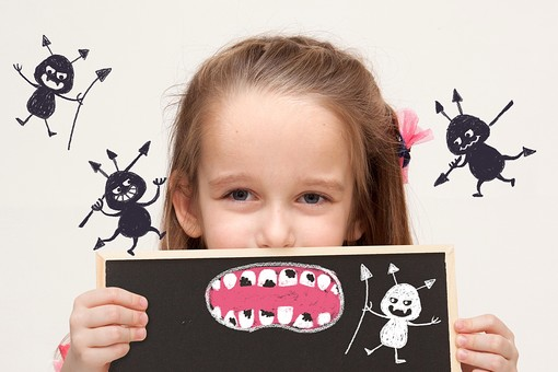 虫歯のイラストの黒板を持つ女の子の写真