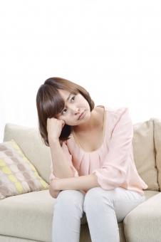女性 女 人物 人 人間 日本人 困る 悩む 考える 困り顔 ストレス 失敗 問題 疲労 過労 心地よい くつろぐ ゆったり リラックス 休日 休み 室内 ソファー かわいい クッション 座る  mdjf003