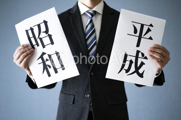 平成と昭和をかざす男性の写真