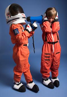 背景 ダーク ネイビー 紺 子ども こども 子供 2人 ふたり 二人 男 男児 男の子 女 女児 女の子 児童 宇宙服 宇宙 服 スペース スペースシャトル 宇宙飛行士 飛行士 オレンジ 希望 夢 将来 未来 体験 職業体験 職業 小道具 小物 ヘルメット 被る うるさい 煩い 五月蠅い 拡声器 マイク ハンドマイク 叫ぶ 大音量 ボリューム 全身 立つ 立 外国人  mdmk009 mdfk045