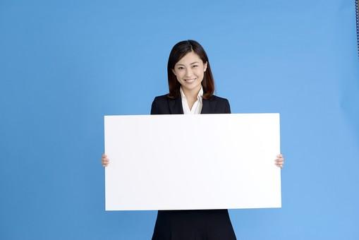 人物 女性 日本人 20代 若者  ビジネス スーツ 黒 紺色 セミロング  OL 社会人 会社員 ビジネスマン 就活  就職活動 真面目 ポーズ 屋内 スタジオ撮影  ブルーバック 上半身 ボード 白紙 メッセージ 持つ 案内 お知らせ 伝える コピースペース テキストスペース 笑顔 mdjf013