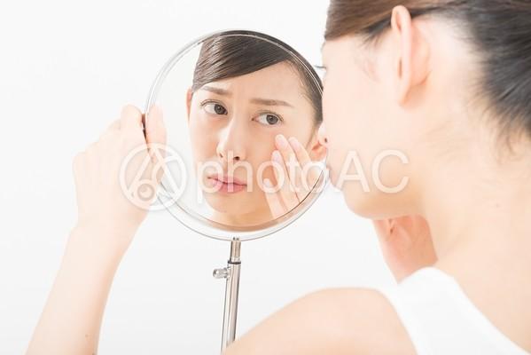 鏡で肌をチェックする女性(鏡越し)3の写真