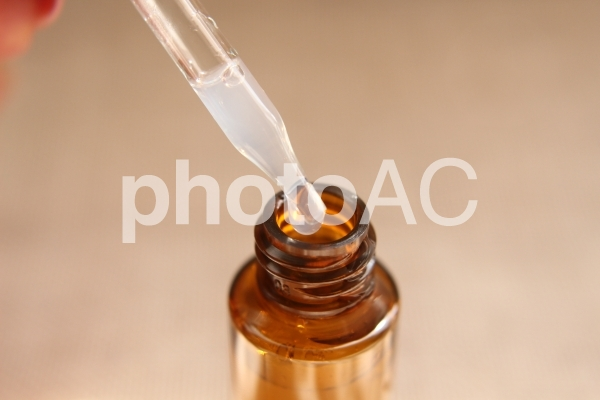 スポイトから滴る美容液の写真