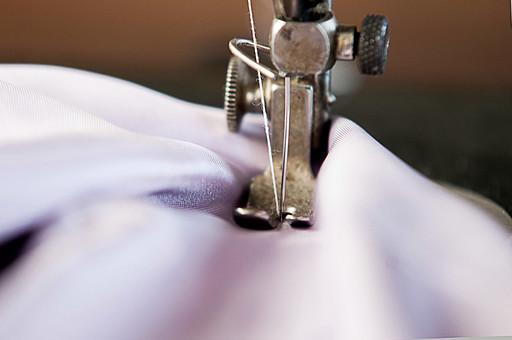 アップ 接写 屋内 室内 裁縫 洋裁 ソーイング 縫製 服 洋服 服作り 手芸 クラフト ハンドクラフト 家事 作業 仕事 デザイナー ミシン アンティークミシン ソーイングマシン 縫う ミシンを掛ける ミシンをかける 布 生地 ミシン針 押え金 ボケ