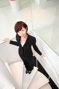 ビジネス 仕事 会社 ビル 建物 建築 建築物 螺旋階段 上る 下る カメラ目線 手すり 見上げる ガラス 透明 上下 1階 2階 床 スーツ 会社員 女性社員 ビジネスマン 女性 女の人 成人 20代 日本人 mdjf002