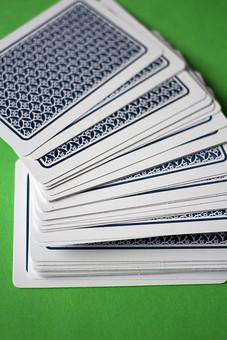 トランプ カード ゲーム 札 絵札 娯楽 グリーンバック 緑背景 机 テーブル 屋外 青 裏側 裏 模様  柄 手品 マジック 遊び  重ねる 重なり 配る 切る カードゲーム アップ  斜め 螺旋 ねじれ