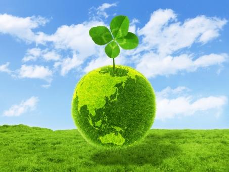夏の青空と草原と四葉のクローバーと世界規模の環境ビジネスの写真