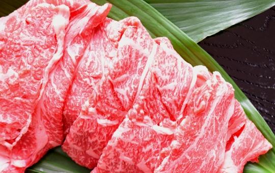 葉ランに載せた和牛肉、生肉、黒背景の写真