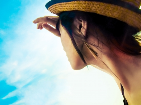 青空を見上げる女性の写真