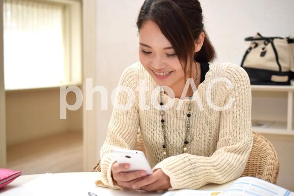 笑顔でスマホを操作する女子高生の写真