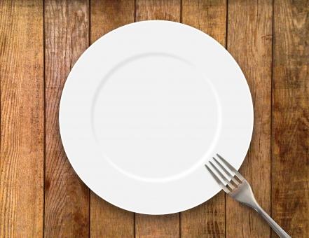 白い皿とフォーク木目背景の写真