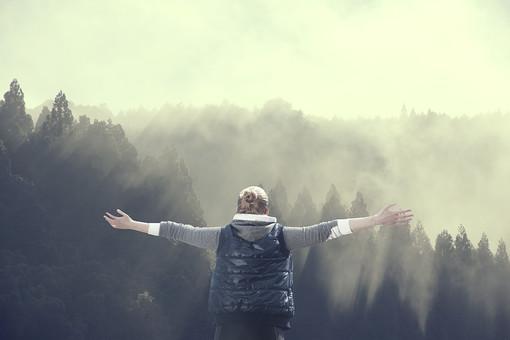 山に向かって手を広げる女性の写真