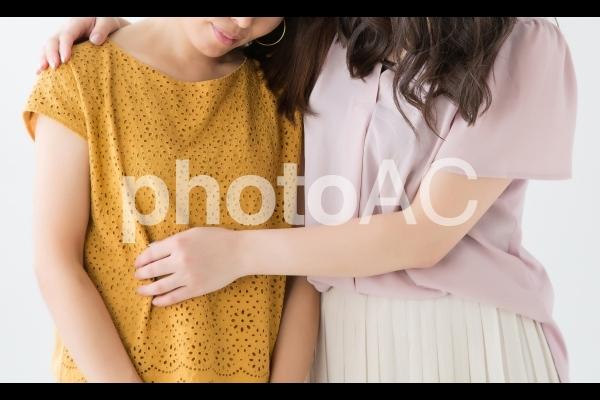 泣く友達を慰めるの写真
