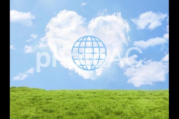 地球儀とハート型雲と草原の写真