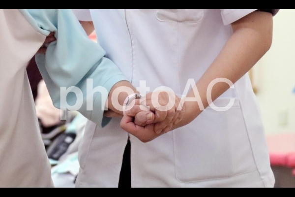 シニア女性を支える介護士の優しい手の写真