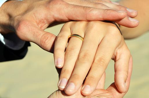 人物 外国人 新郎 新婦 花婿 花嫁 男性 女性 男の人 女の人 成人 男女 カップル 新婚 アベック 夫婦 夫 妻 ポーズ 手を取る 指輪 指輪の交換 マリッジリング 金 儀式 嵌める 手 指 幸せ 結婚式 屋外 室外 自然 砂浜