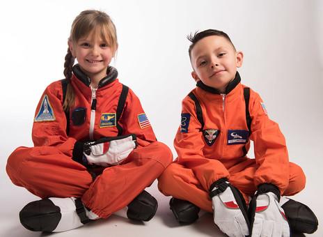 グレーバック 背景 グレー 子ども こども 子供 2人 ふたり 二人 男 男児 男の子 女 女児 女の子 児童 宇宙服 宇宙 服 スペース スペースシャトル 宇宙飛行士 飛行士 オレンジ 希望 夢 将来 未来 体験 職業体験 職業 全身 姿勢 座る 胡座 胡坐 あぐら 笑顔 スマイル 外国人  mdmk009 mdfk045
