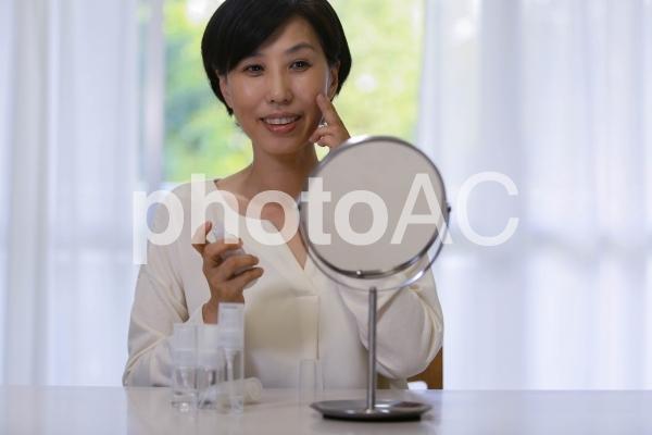 鏡の前で肌のお手入れをする女性の写真