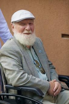 病院 医院 診療所 屋外 外 外国人 白人 男性 老人 高齢 高齢者 おじいさん おじいちゃん 髭 ヒゲ ひげ 白髪 車椅子 車いす 座る 乗る 乗せる 上着 ジャケット ハンチング帽 上半身 カメラ目線 mdjms016