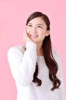 人物 女性 日本人 若者 若い  20代 美人 かわいい ロングヘア カジュアル  ラフ 私服 セーター ニット 屋内  スタジオ撮影 背景 ピンク ピンクバック ポーズ  おすすめ 上半身 笑顔 見上げる 頬 手を当てる 期待 希望 嬉しい うれしい やったー mdjf007