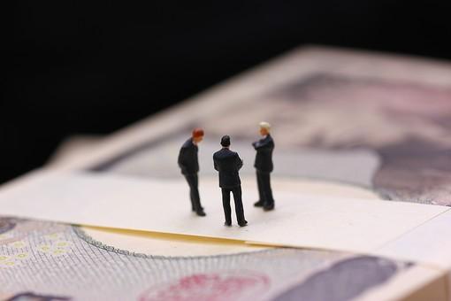 1万円札束の上に小さなビジネスマン9の写真