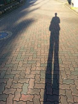 影絵 かげ シャドー shadow Schatten 光 輪郭 陰り 陰影 コントラスト シルエット 光源 一人 ひとり 足長 足長おじさん あしなが 伸びる 足が長い 長い 太陽 地面 タイル 孤独 寂しい 哀愁 あしながおじさん 足 脚 背景素材