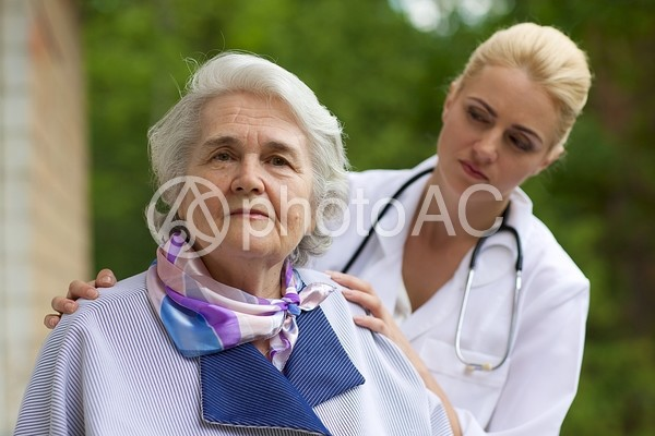 外国人高齢女性の肩を触る外国人女医2の写真