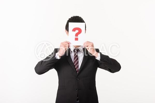 クエスチョンマークで顔を隠すビジネスマン2の写真