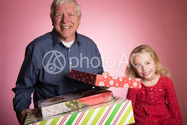 プレゼントを抱える祖父と孫3の写真